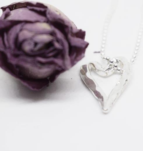 silverhjärta i kdeja på vit botten med lila ros bredvid