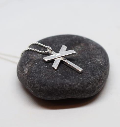 ledkryss i silver på mörkgrå sten
