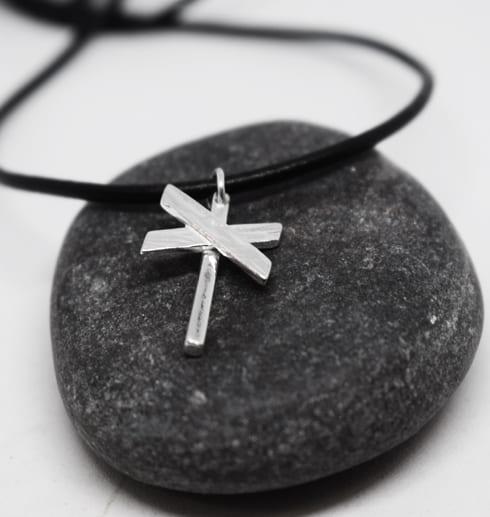 ledkryss i silver med läderrem på mörkgrå sten