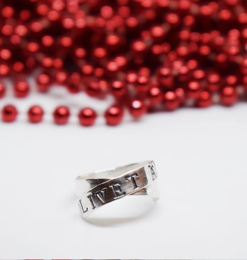 silverring med text på vit bakgrund med röda pärlor bakom