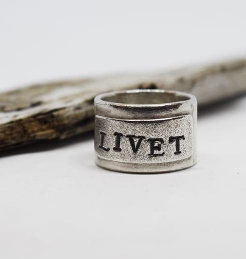 Bred ring i silver med texten LIVET framför en trädbit