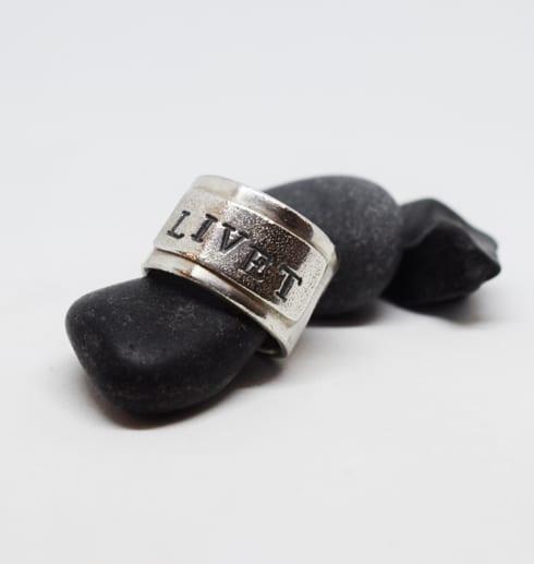 Bred ring med texten LIVET på grå stenar med vit bakgrund