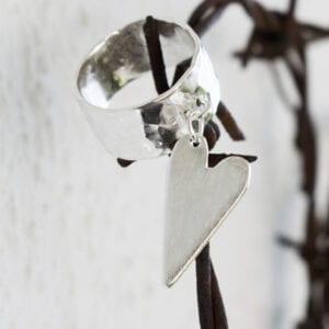 silverring med löst hängande hjärta som sitter på ett traggtrådshjärta