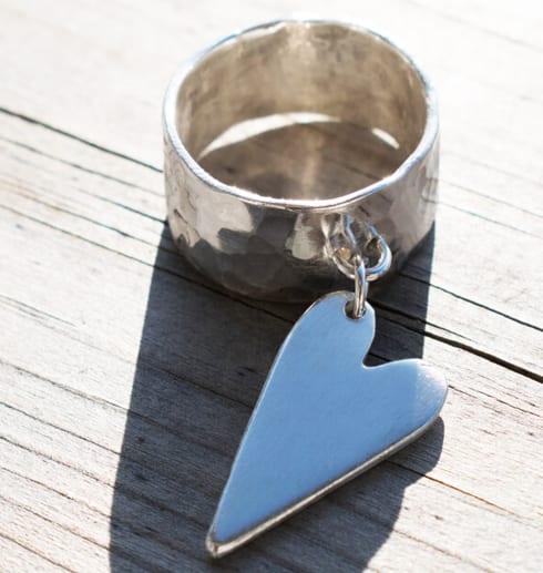 silverring med löst hängande hjärta på trä utomhus