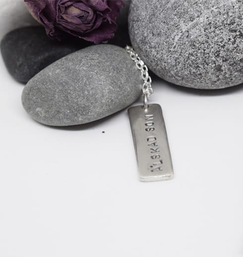 silverhalsband på it botten med stenar bakom