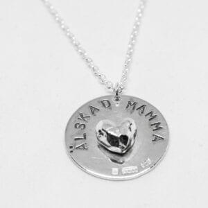 silverhalsband med texten ÄLSKAD MAMMA och hjärta på vit bakgrund