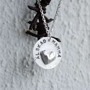silverhalsband med hjärta och texten ÄLSKAD MAMMA hängande på taggtråd utomhus