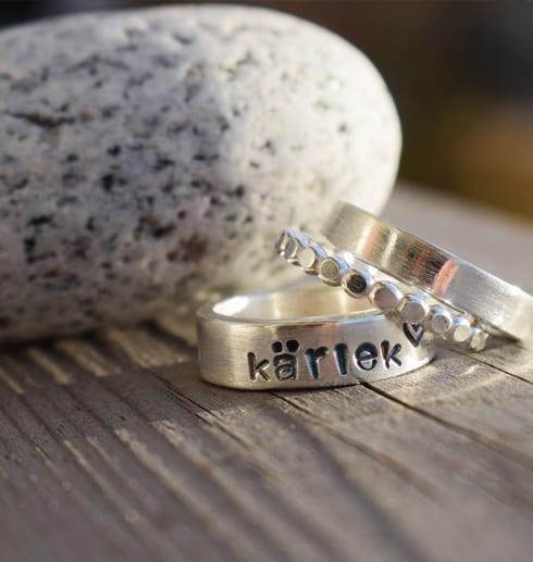 tre silverringar en med texten kärlek på trä med sten bredvid