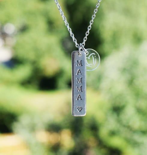 silverhalsband med texten MAMMA hängande i luften utomhus