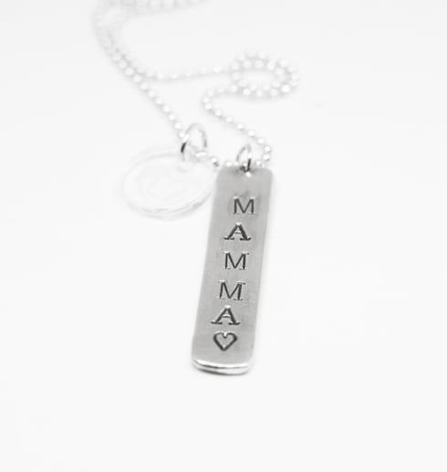 silversmycke med texten MAMMA på vit bakgrund