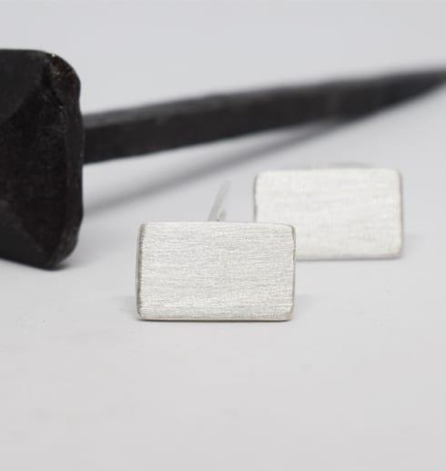 manchettknappar i silver på vit botten med stor järnspik bakom