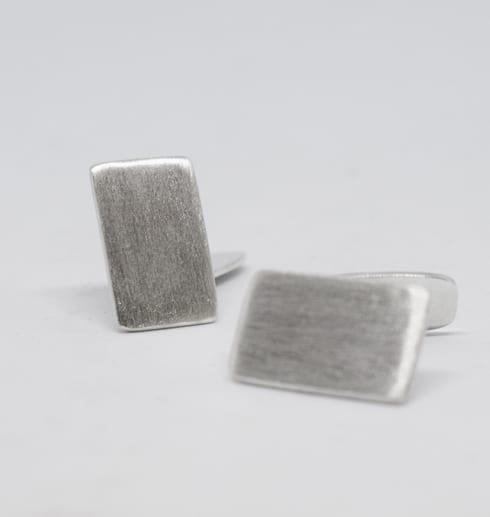 manchettknappar i silver på vit botten