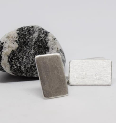 manchettknappar i silver med gråvit sten bakom