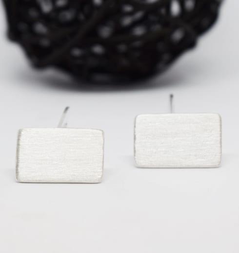 silvermanchettknappar på vit botten med trådboll bakom