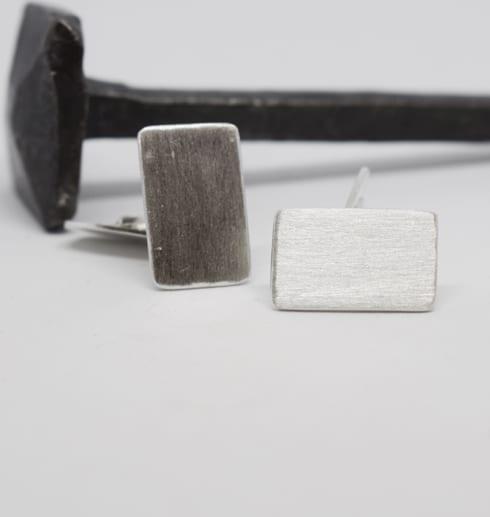 manchettknappar i silver på vit botten med järnspik bakom