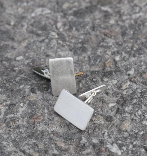 manchettknappar i silver på grå botten