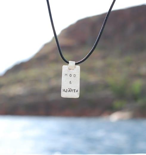 silverbricka med text i läderband utomhus vid hav