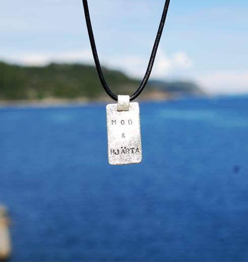 silverhalsband med text hängande utomhus vid havet