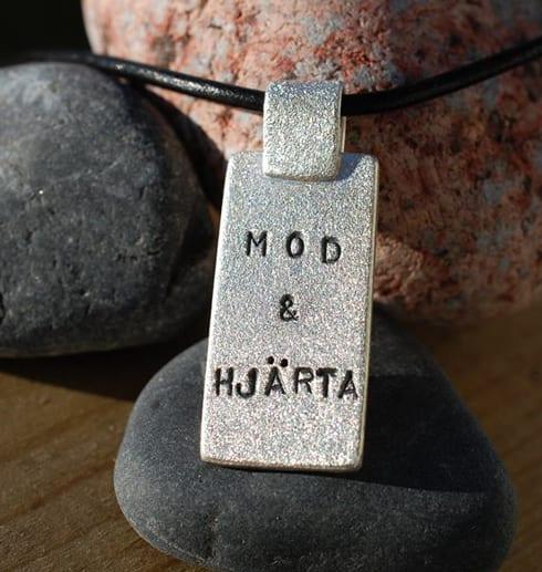 borstad silverbricka med text i läderrem på stenar utomhus i