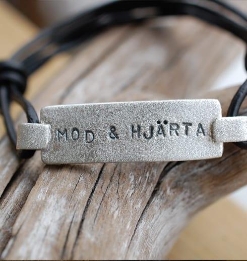 borstat silverarmband med text på trädgren med läderband