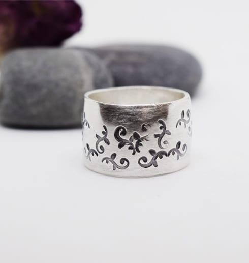 bred silverring med mönster på vitbakgrund med stenar bakom