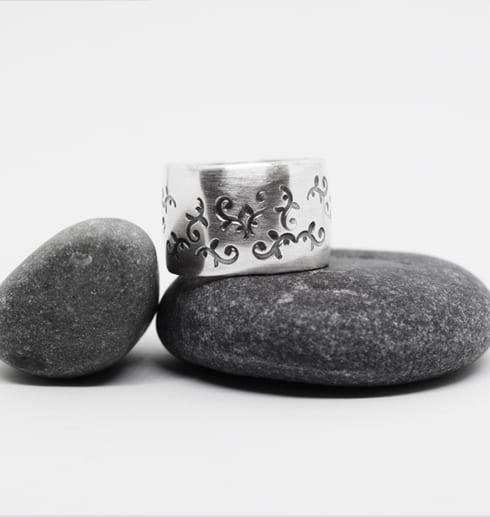 bred silverring med mönster på stenar
