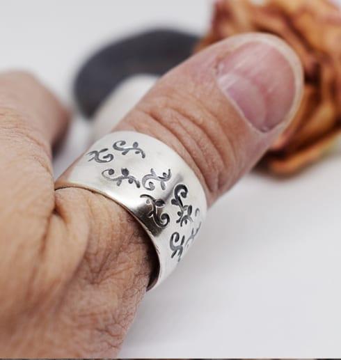 bred silverring med mönster på tumme