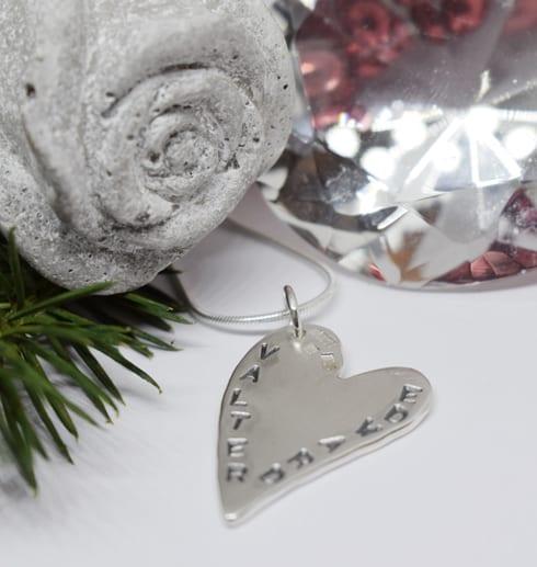 silverhjärta med text med betongros, grankvist och en diamant bredvid