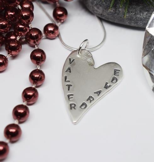silverhjärta med namn på vit botten med röda kulor, sten och diamant i kanterna