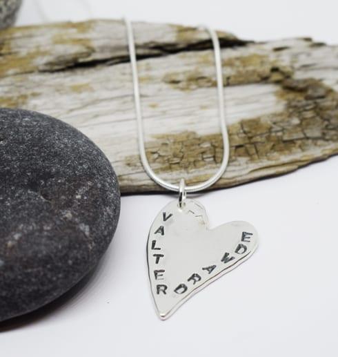 silverhjärta med namn med sten och träbit bredvid