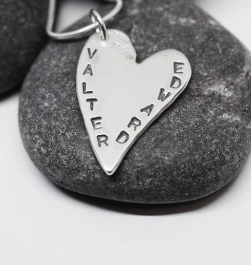 silverhjärta med namn på grå sten