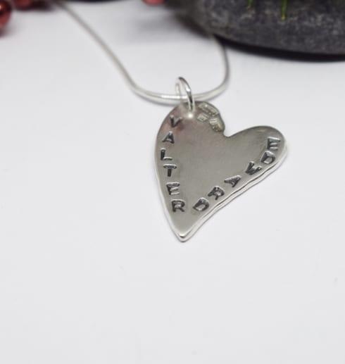 silverhjärta med namn på vit bakgrund med sten i ena hörnet