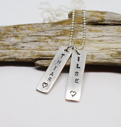 två namnbrickor i silver mot träbit