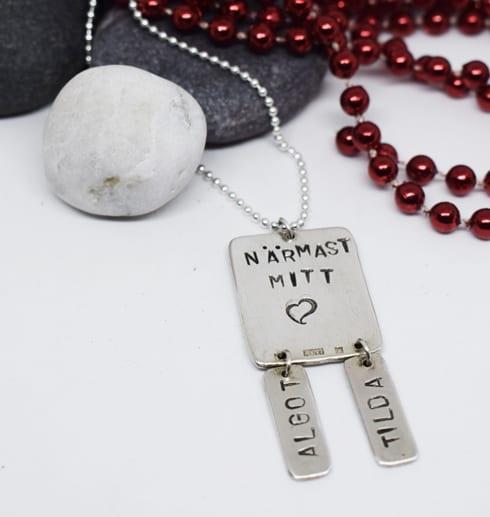 silverhalsband med text med stenar och röda kulor bakom