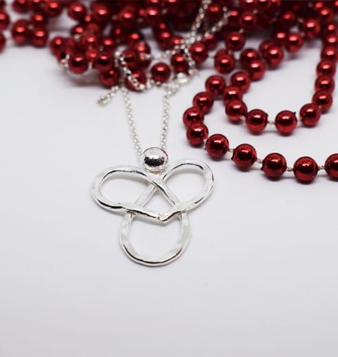 silverhalsband i form av en ängel med röda pärlor bakom