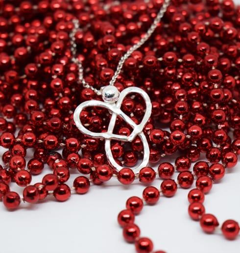 silverhalsband i form av en ängel på röda pärlor