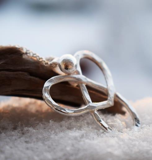 silverängel i kedja på trägren i snö utomhus
