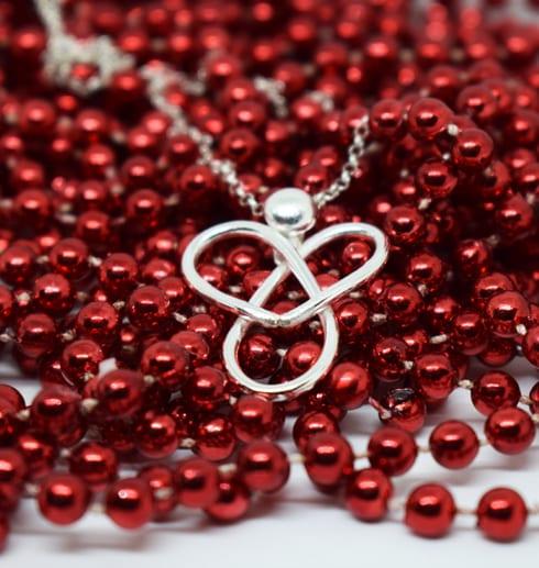 ängel i silver på röda pärlor
