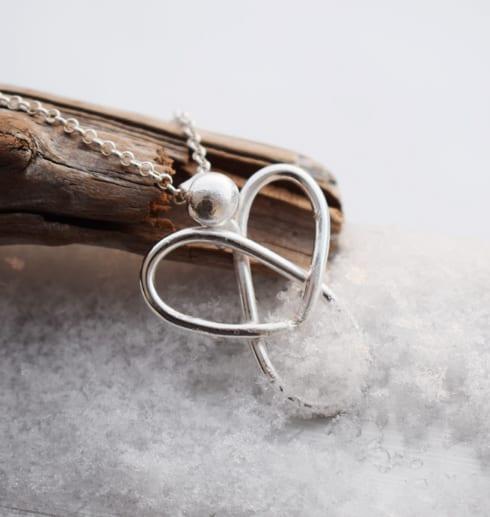 silverängel i kedja på träbit och snö utomhus