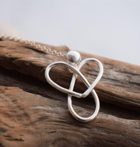 silverhalsband i form av en ängel på träbit utomhus