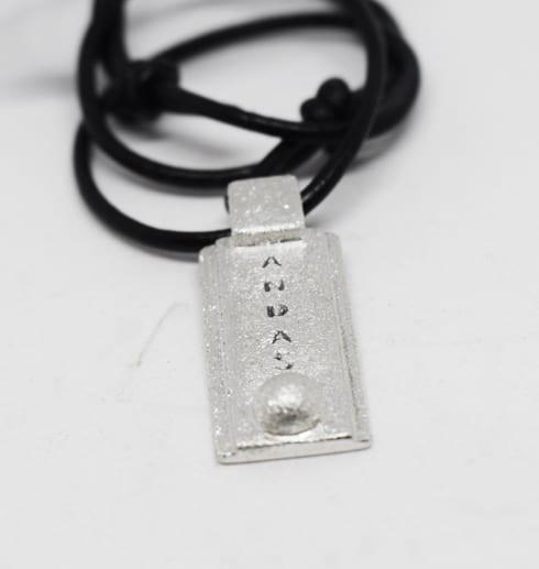 silversmycke med texten ANDAS i läderrem med vit bakgrund