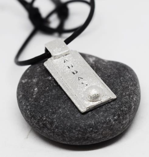 silversmycke med texten ANDAS på grå sten