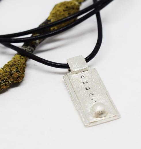 silversmycke med texten ANDAS i läderrem på vit bakgrund med trädgren bakom