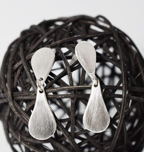 silverörhängen på en svart trådboll
