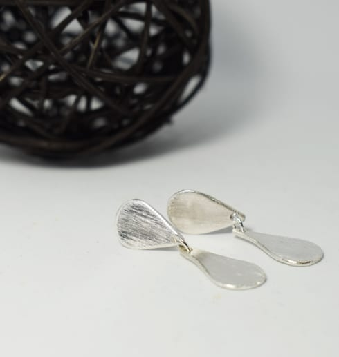silverörhängen på vit botten med svart trådboll