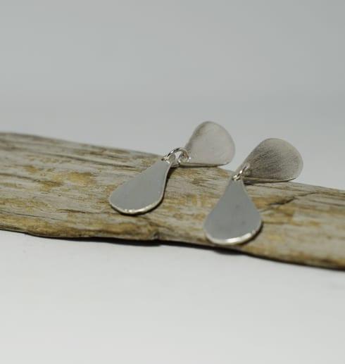 silverörhängen mot träbit