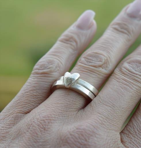 silverringar med hjärta på finger utomhus