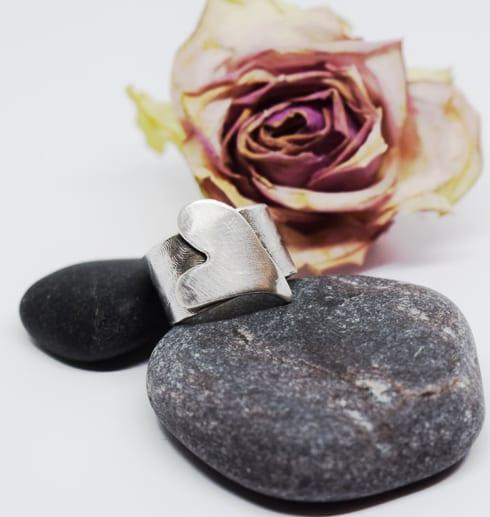 bred ring med hjärta på stenar med ros bakom