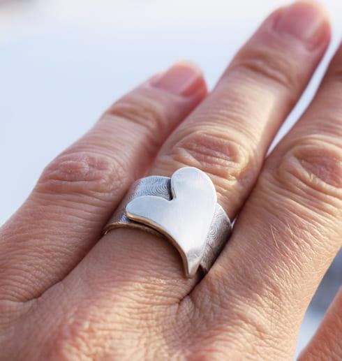 bred silverring med hjärta på finger utomhus
