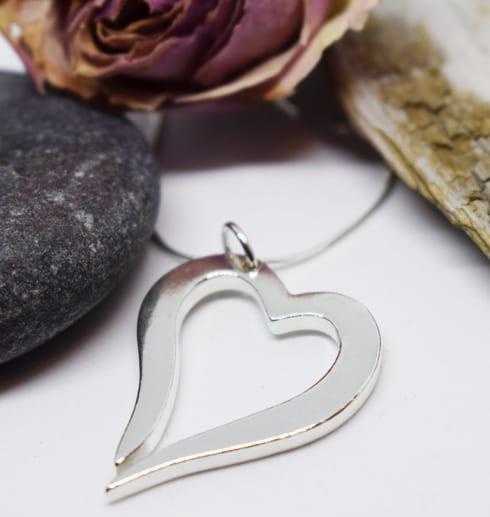 silverhjärta i kedja på vit bakgrund med stenar, ros och träbit bakom